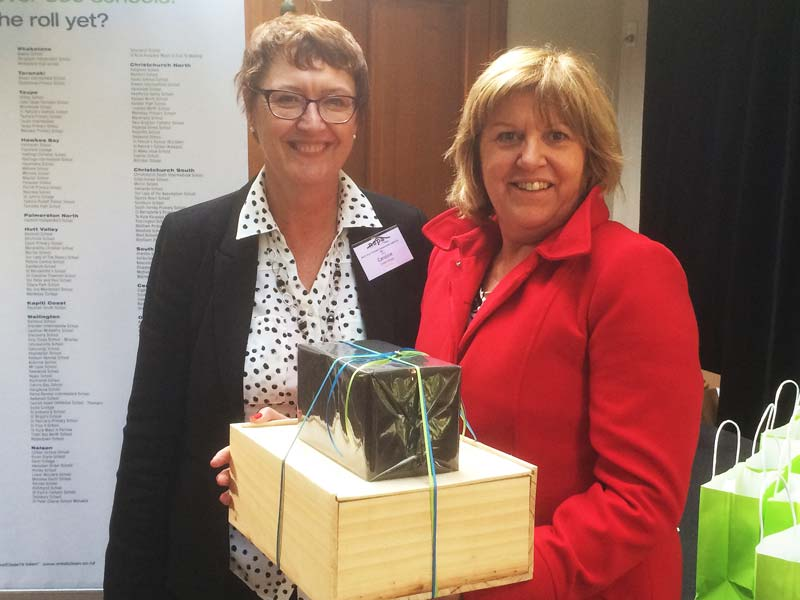 Liz Walker, Principal at St Leo's School, Devonport, receives a gift hamper from Caroline Wedding (left), Auckland North Shore Regional Manager.