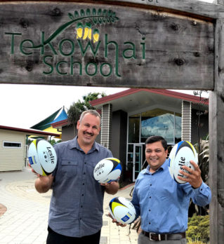 Tony Grey, Te Kowhai School Principal, receives the rugby balls from Nivitesh Kumar, CrestClean's Waikato Regional Manager.