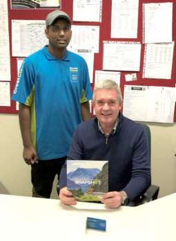 Bruce Tilby receives a copy of CrestClean's anniversary book from Ashitosh Prasad.