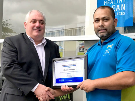Fiza Rahiman receives a Certificate of Achievement from the Master Cleaners Training Institute. Making the presentation is Dries Mangnus, CrestClean's Auckland Central Regional Manager.