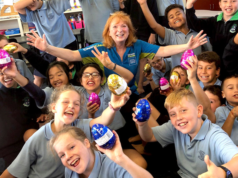 Deborah Herries hands out Easter eggs to children who won the Cleanest Classroom competition at St Patrick's School, Napier.