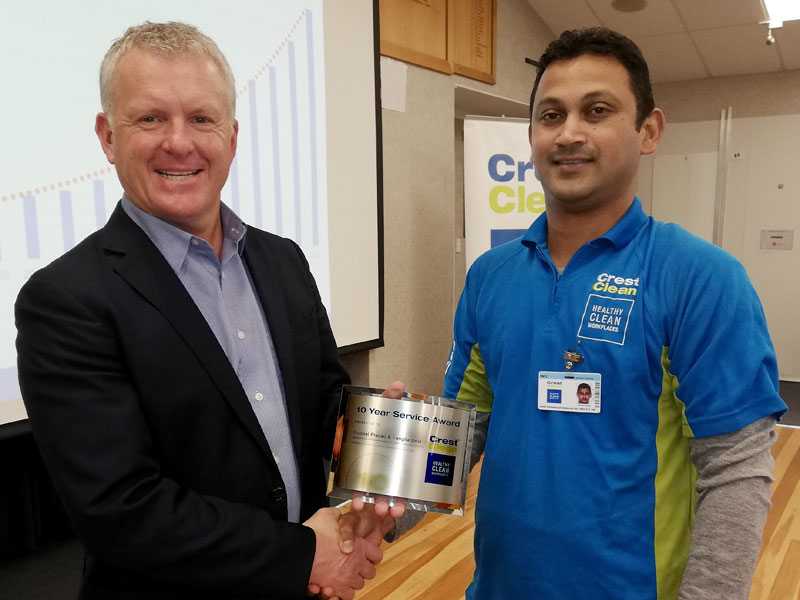 Praneel Prasad receives his 10-year long service award from Grant McLauchlan, CrestClean's Managing Director.
