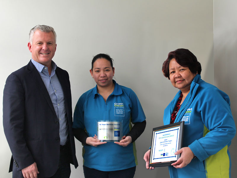 Agnes Vasquez and her daughter Christine receive their long service award from Grant McLauchlan, CrestClean's Managing Director.