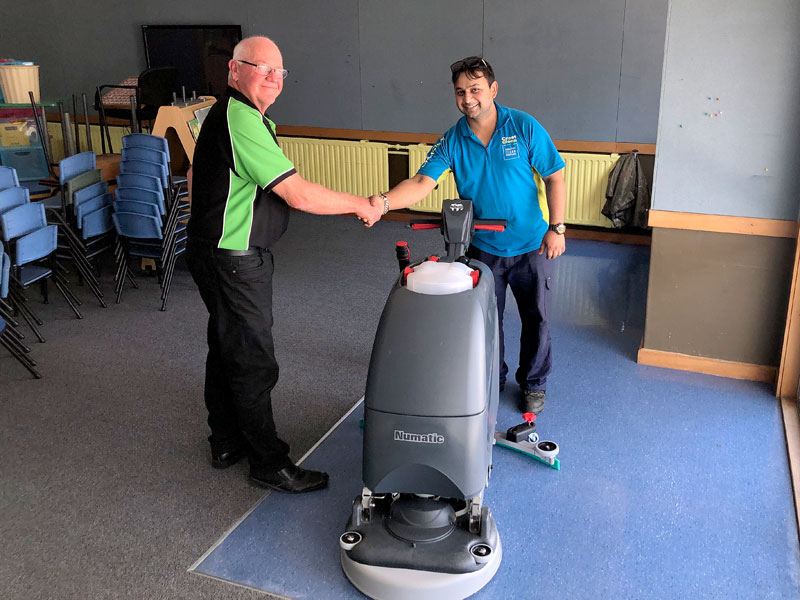 Sandeep Kumar receives his new floor scrubber from Dave McLeod.