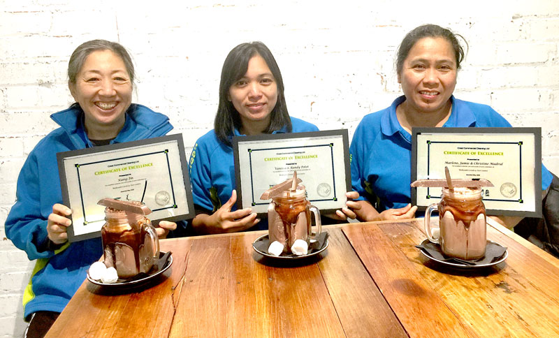 Kim Jin, Vanessa Potot and Marlene Madrid celebrate receiving their awards over a hot chocolate.