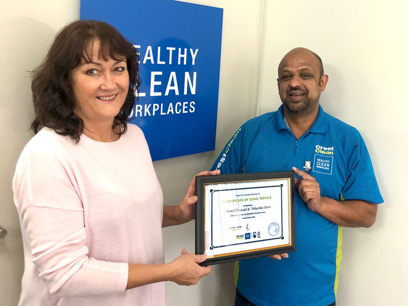 Anmol Prasad receives his 10-year long service award from Linda Hill, CrestClean's Auckland East Regional Manager.