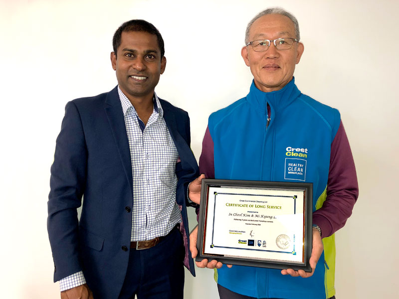David Kim receives his long service award from Yasa Panagoda, CrestClean's Christchurch North Regional Manager.