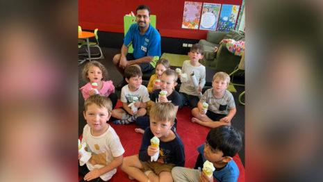 School children eating ice creams.