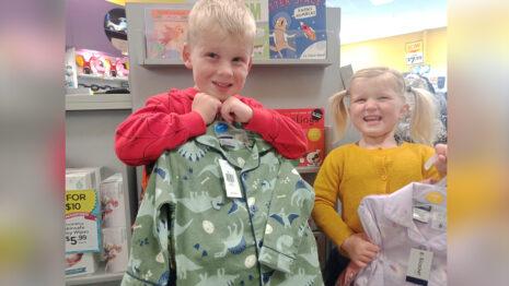 Children holding pyjamas.